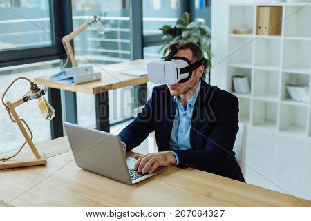 Technological innovations. Smart pleasant confident man wearing 3d glasses and working on a laptop while testing new technologies