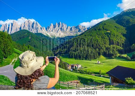 Woman enjoy the view of Dolomites in Val di Funes valley, Santa Maddalena touristic village, Dolomites, Italy, Europe