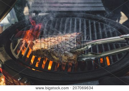 Tbone Beef Steak Being Cooked On A Grill With Tongs