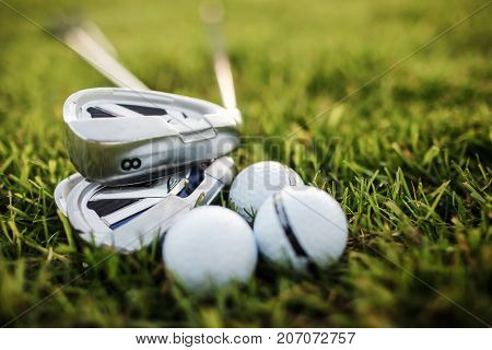 Golf balls and golf club on green grass