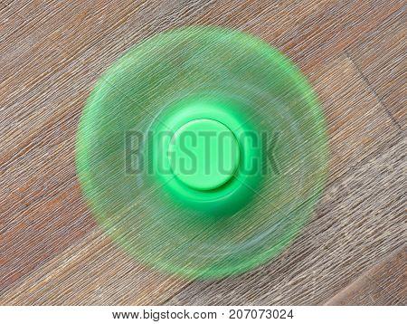 Image of Fidget finger spinner stress toy - Green spinner on a wooden desk