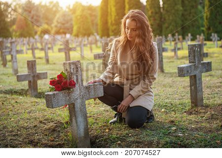 Sad woman in the cemetery, holding a bouquet of roses in her hand
