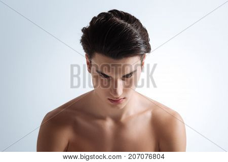 Being in frustration. Enigmatical man bowing head and looking downwards while sitting isolated on white