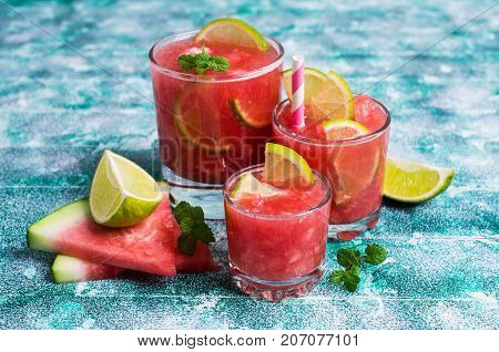 Cold watermelon drink with lemon and mint on a wooden background. Selective focus.