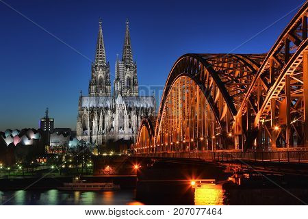 Cologne in the night. Cathedral on the night cloudless blue sky and the railway bridge. Cologne, Germany.