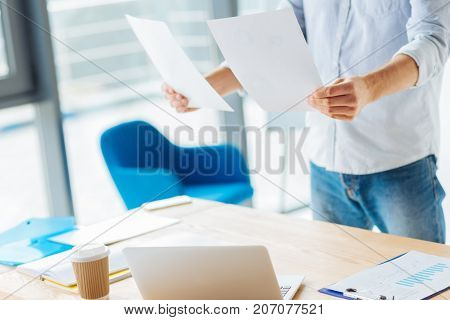 Preparing for work. Competent worker standing near his table and holding papers while keeping it in the air