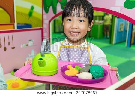 Asian Chinese Little Girl Role-playing At Kitchen