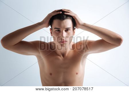 Need new hairstyle. Serious youth putting hands on his head while holding static and pressing lips