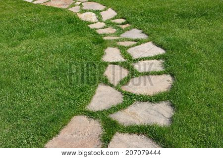 Stone path on a green grassy lawn. The way paved single stones among a green grass.