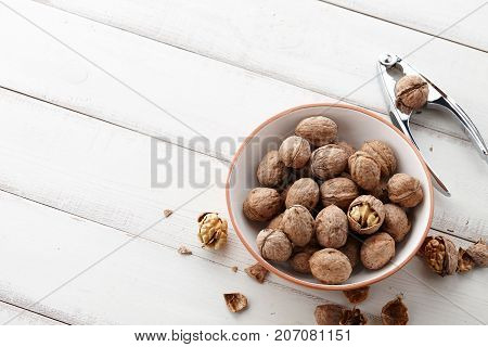 Fresh walnuts bowl, nutshell and nutcracker on white wooden background, space for texting