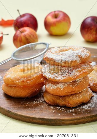 Appetizing homemade donuts with apples and powdered sugar on wooden board