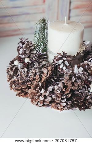 Christmas candlestick on the table, decoration with cones