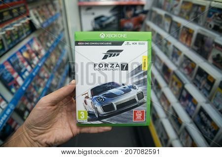 Bratislava, Slovakia, october 2, 2017: Man holding Forza 7 videogame on Microsoft XBOX One console in store
