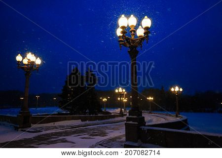 Street lights and road illuminated street lamps and snowing in winter at night.