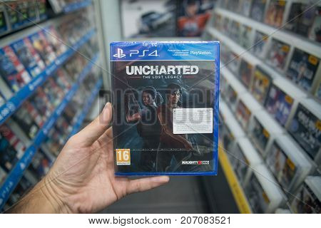 Bratislava, Slovakia, october 2 2017: Man holding Uncharted the Lost Legacy videogame on Sony Playstation 4 console in store