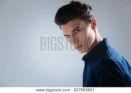 Enigmatical look. Handsome student wearing blue shirt and bowing head while standing over grey background