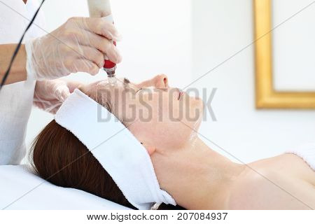 Microneedle mesotherapy, treatment woman at the beautician. Beautician performs a needle mesotherapy treatment on a woman's face