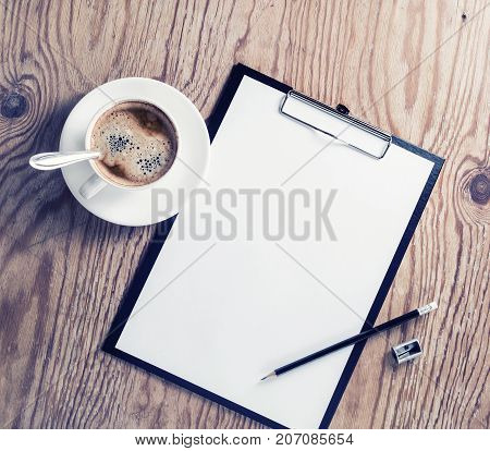 Blank letterhead clipboard coffee cup pencil and sharpener. ID template on wood table background. Mock up for placing your design. Top view.