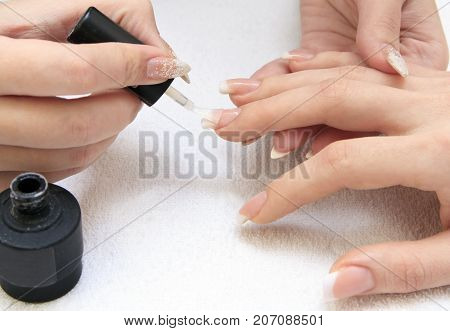manicure making - female hands covering of transparent enamel