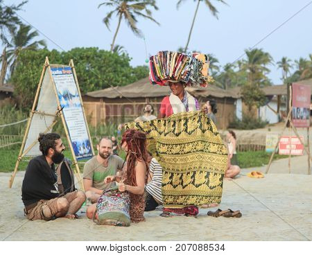 Goa India - February 15 2016: Woman seller at the beach Arambol offers its goods to tourists