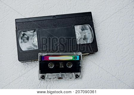 cassette audio and black video cassette on a gray table