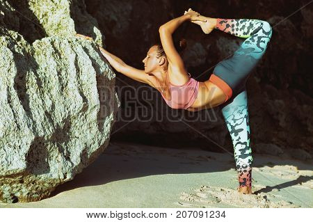 Meditation on rock background. Young active woman stand in yoga pose on beach rock stretching to keep fit and health. Healthy lifestyle outdoor fitness sports activity on summer family holiday.