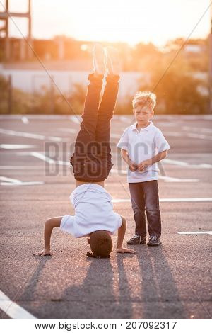 The boy is showing a headstand on the street. Younger brother admires his brother