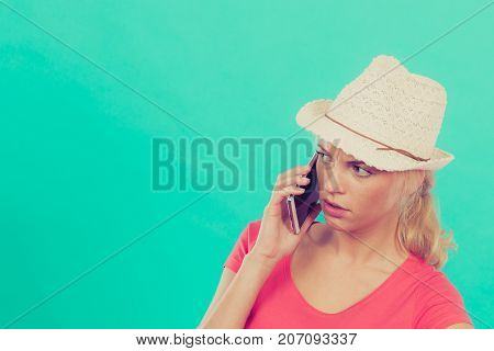 International calls calling friends and family abroad modern technology concept. Confused tourist woman with sun hat talking on phone