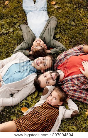 Top view shot of happy family with two children lying on a grassy lawn
