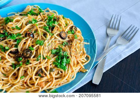 Spaghetti Alla Puttanesca - traditional italian pasta with black olives tuna anchovies capers and parsley. Vegetarian food. Italian cuisine.