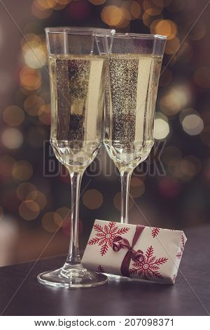Detail of two champagne glasses placed on the table with small nicely wrapped gift box and Christmas tree and lights in the background. Selective focus on the gift box