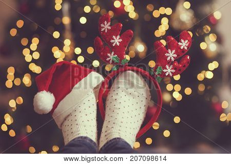 Woman's feet wearing warm winter socks antlers and Santa's hat placed on the table with Christmas tree and Christmas lights in the background. Selective focus on the antlers