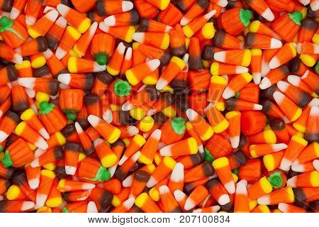 Halloween candy corn with candy pumpkins background