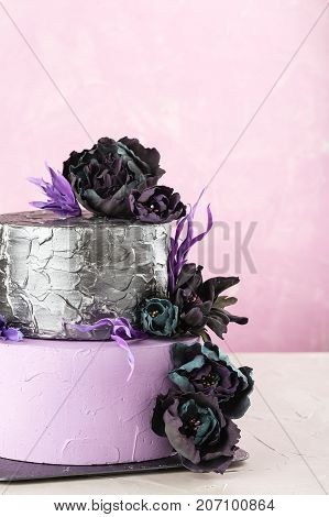 Tiered Wedding Cake With Black Fake Flowers On Pink Background