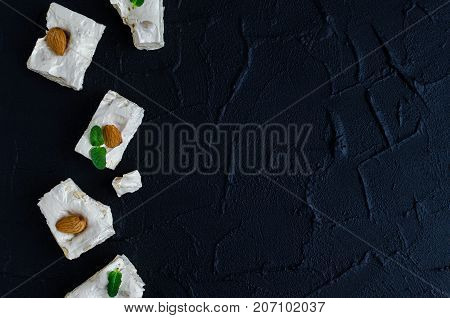 Delicious traditional Italian festive torrone or nougat with nuts on black stone background with place for text. Soft nougat blocks with almonds with fresh mint leaves. Italian sweets. Copy space.