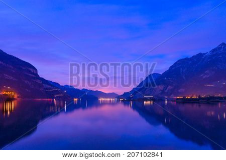 Night landscape. Royal blue. The mountain range the light of lanterns and lamps are reflected in the lake long exposure