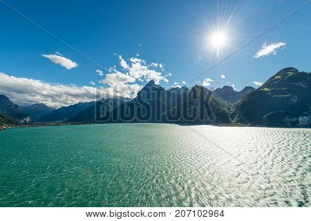 Mountain range. Swiss Alps. Lake Lucerne. White sail on the lake. Aerial landscape in contrasting light of a bright sun. Black and White