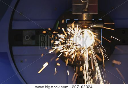 The fiber laser cutting machine cutting the steel pipe with the sparking light.The fire flame from the fiber laser cutting machine.