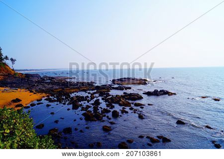 View to the coastline from the hill between Baga beach and Anjuna. Skyline during evening time. A lot of rocks on the sea.