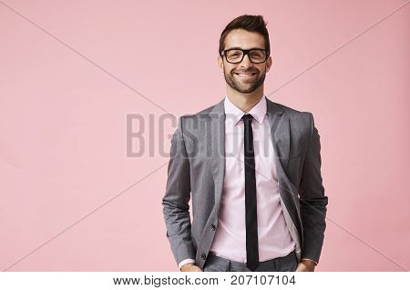 Happy grey suit guy in pink studio portrait