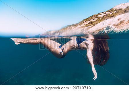 Woman in blue bikini with long hair floating in ocean. Underwater photo