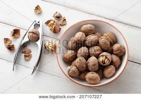 Fresh walnuts bowl, nutshell and nutcracker on white wooden background