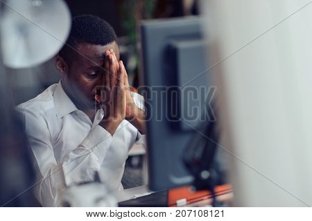 Tired African man sitting at a cafe after a hard workday, squeezing his temples because of headache, working on laptop, looking at the screen with painful expression on his face, trying to concentrate