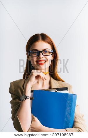 beautiful red-haired girl with glasses looks at the camera and holds a folder in hand on a white background, isolated