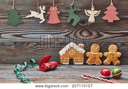 Christmas homemade gingerbread cookies and decoration on wooden background. Gingerbread house and couple - man and woman.