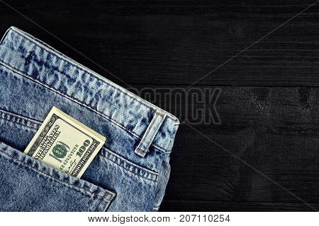 Pocket money. Dollar in hip pocket of worn blue jeans on black wooden background. Close-up. Top view. Copy space. Still life