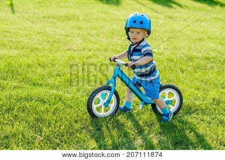 Boy in helmet riding a blue balance bike (run bike). Happy child learning to keep balance on a training bicycle in the garden. Kid playing outside. First day on the bike.