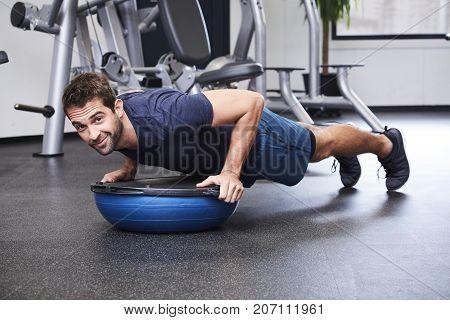 Dude performing press ups on bosu ball portrait