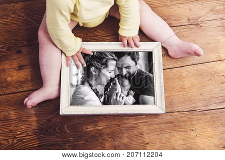 Unrecognizable little baby holding picture frame with photo of young family with little baby girl. Studio shot on wooden background. Fathers day concept.