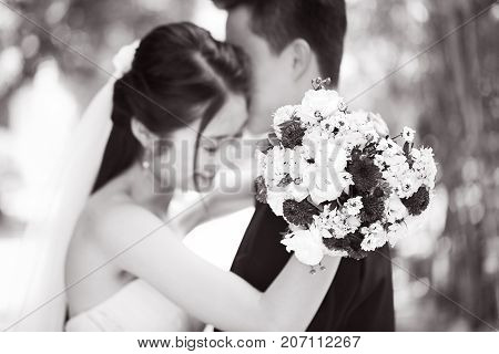 young asian newly wed couple hugging each other during wedding ceremony focus on the bouquet black and white.